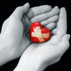image of hands holding a wounded heart