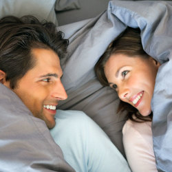 image of happy couple smiling at each other under bed covers