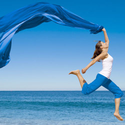 image of woman jumping for joy on the beach