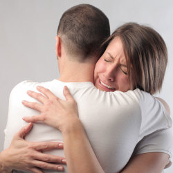 Woman hugging husband after he has admitted he is gay