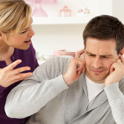 image of husband with fingers in ears listening to nagging wife