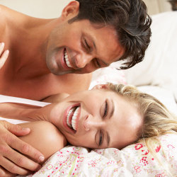 image of happy couple lying in bed