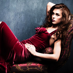 image of woman in gorgeous burgundy dress lying on couch