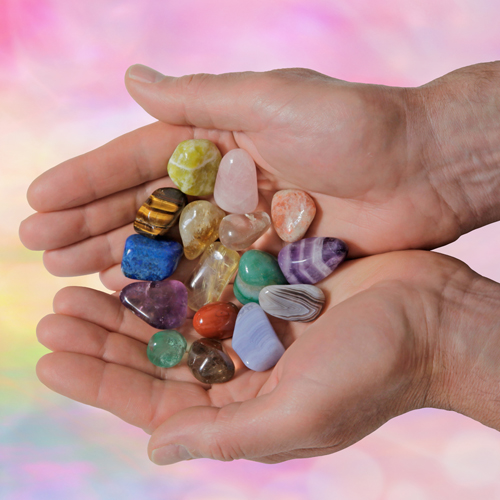 image of a hand holding healing crystals