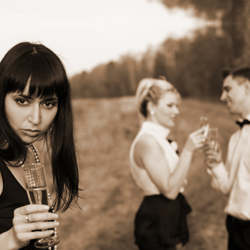 image of a woman glaring away as her boyfriend speaks to another woman with champagne in their hands