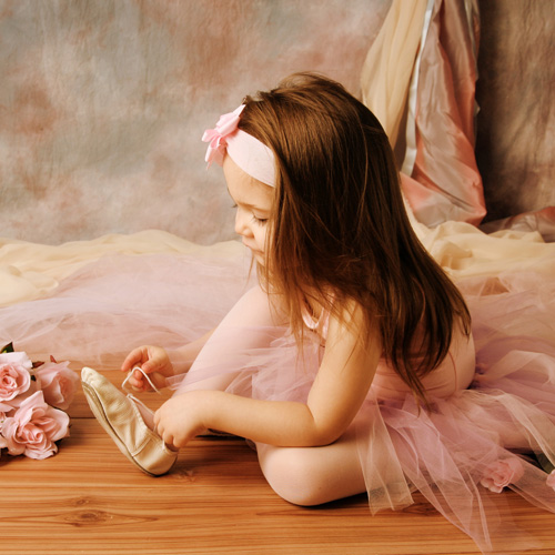 image of a little ballerina girl in a pink tutu putting on her ballet shoes