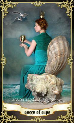 image of a woman in a green dress holding the queen of cups tarot