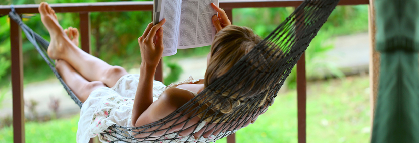 image of a relaxed woman reading a book on a hammock
