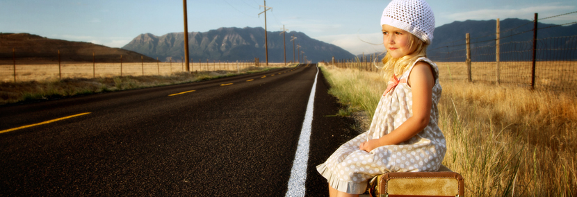 image of a young girl sitting on the side of a road ready to go on a journey