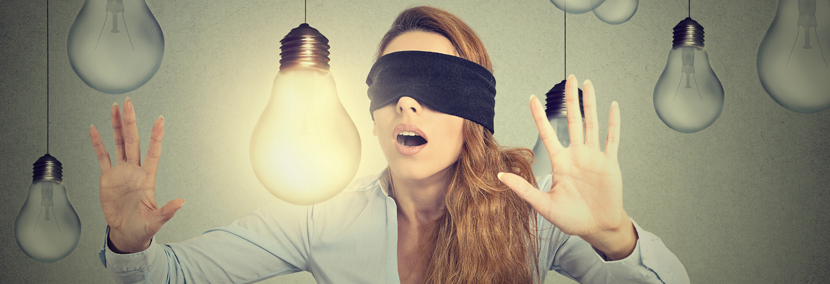 image of a blindfolded woman wandering through lightbulbs