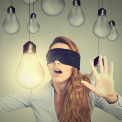 image of a blindfolded woman wandering through lightbulbs trusting her intuition